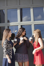 Group of women holding frozen latte drinks.