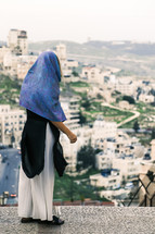 a woman with a scarf over her head looking out at town below