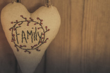 A heart shaped pillow with the word Family on it