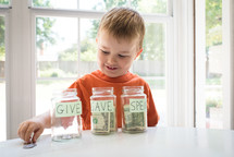 a toddler boy and give, save, spend jars
