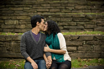 man and woman sitting outdoors kissing