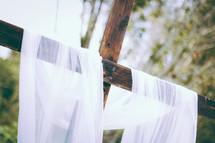 white shroud on a wooden cross