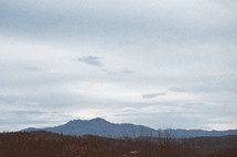 view of mountain top in the distance from another mountain