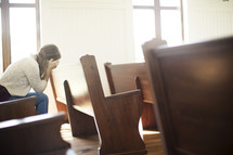 a woman siting in a church pew hiding her face