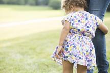 toddler girl hugging mother's leg
