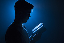 a man reading a Bible illuminated in darkness