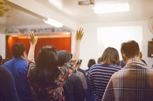 people standing with hands raised at a worship service