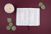 candle, leaves, and open Bible on a maroon background