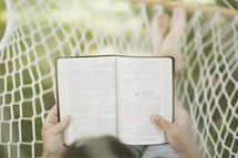 woman reading a Bible in a hammock