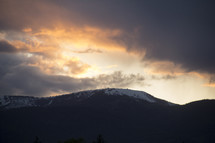 a sky at sunset over a snow capped mountain