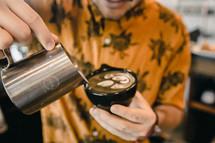 barista pouring creamer in a mug