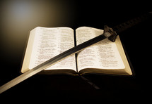 sword lying on the pages of a Bible