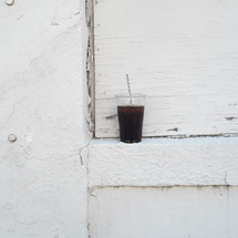plastic cup of soda and straw on a ledge