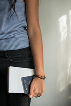 young woman holding a Bible and passport at her side