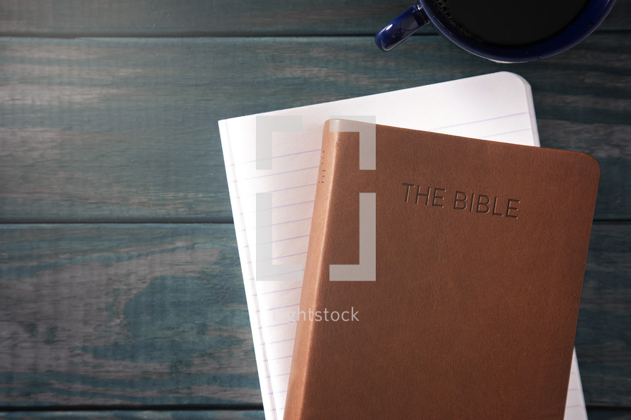 leather Bible, notebook, and coffee cup on a wood background