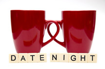 words date night and two red coffee mugs