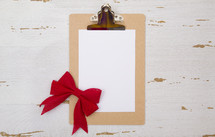 clipboard with white paper and red bow
