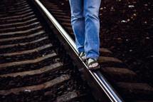 A person walking a rail along a railroad track.