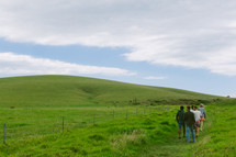 A group of people walking through a countryside covered in green grass.