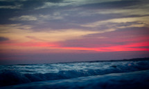 Ocean waves rolling into shore under a red hazy sky.
