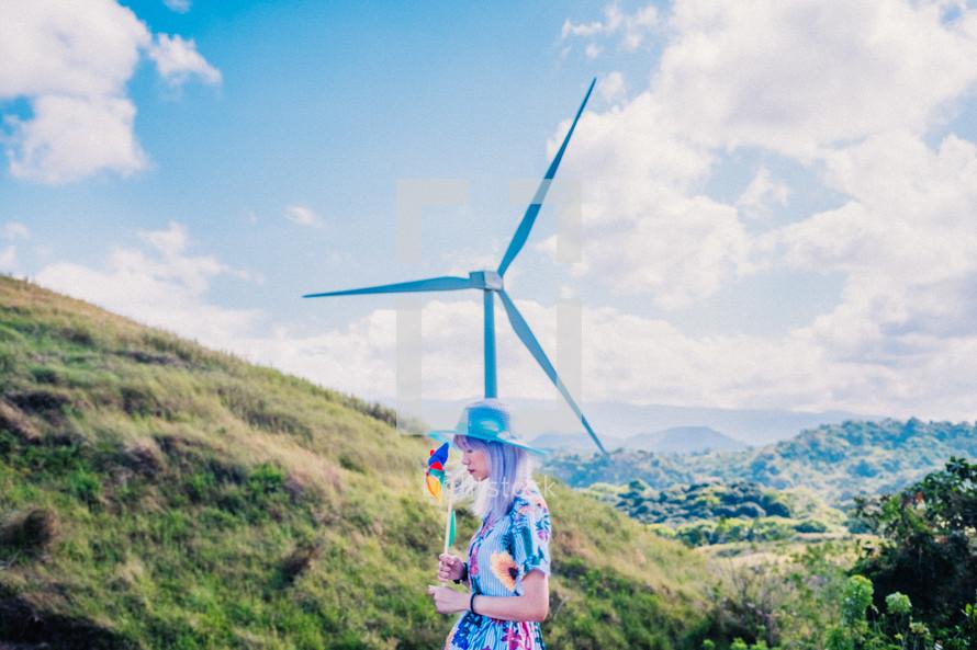 a woman holding pinwheels beside a wind turbine