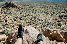 a man sitting on a rock looking out at the desert