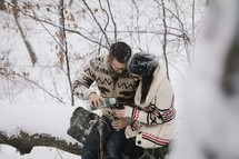 a couple drinking hot cocoa in the snow outdoors