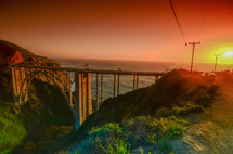 bridge crossing a ravine along a shore at sunset