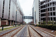 Railroad tracks in between two office buildings.