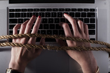 hands tied to a computer keyboard.