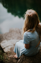a young woman sitting on a rock looking out at a pond