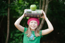 a child holding a stack of books on her head