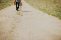 woman walking down a dirt road carrying suitcases