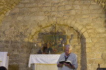 a man reading scripture in front of an altar