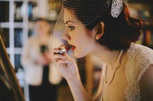 a bride putting on red lipstick