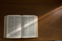 A Bible open to the Book of Isaiah on a wood surface.