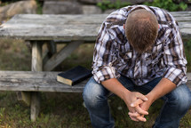 a man praying at a picnic table