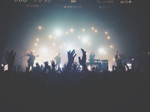 silhouettes of raised hands of audience members at a concert