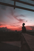 silhouette of a man sitting outdoors at sunset and city view
