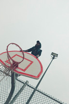 teen boy sitting on the top of a basketball goal