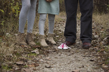 Family standing on a trail outside with a pair of baby shoes.