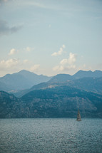 sailboat in water in front of a mountainous island