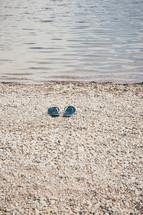 flip flops on a beach near water