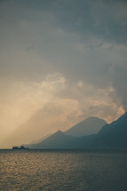 rays of sunlight shining through the clouds onto the ocean and mountains