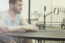 man reading and pondering while sitting at a table at an outdoor cafe