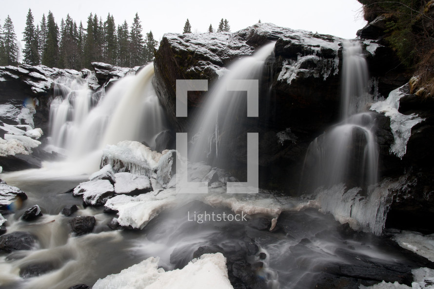 Waterfalls over rocks in an icy stream.