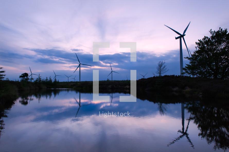 Wind turbines along a pond.
