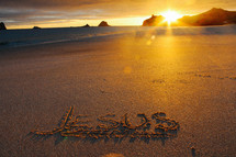 Jesus written in the sands of a beach at sunset