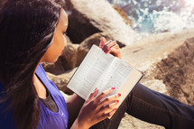 woman reading a Bible on a beach