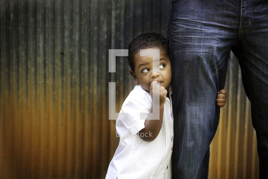 Little boy holding onto his dad's leg